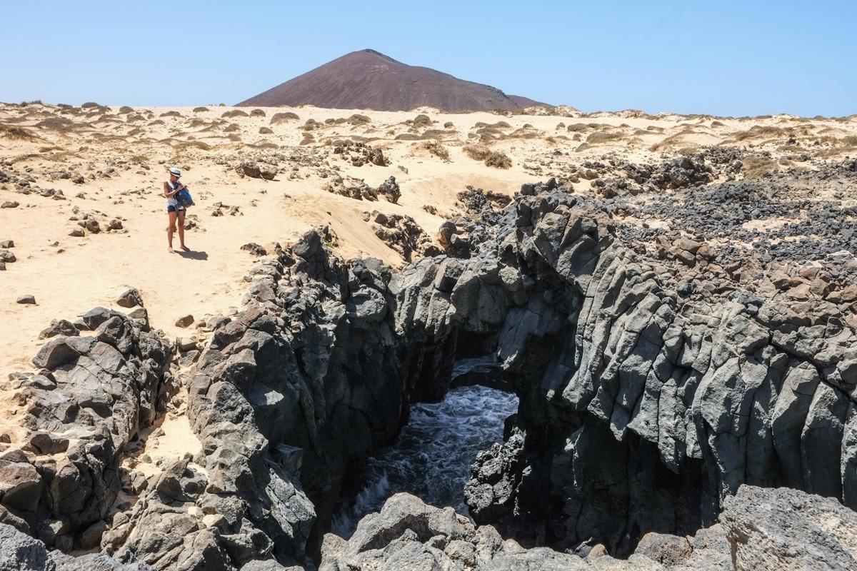 Parte del monumento natural de Los Caletones con un volcán al fondo.