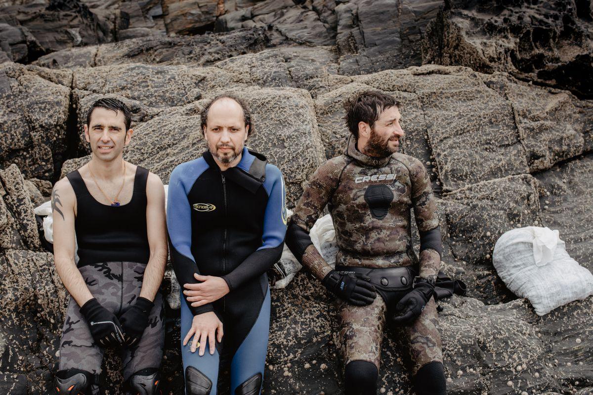 Sergio, Óscar y Alberto, de 'Mar de Ardora', en las rocas de la orilla de la playa al terminar la jornada de recogida de algas, en Galicia.