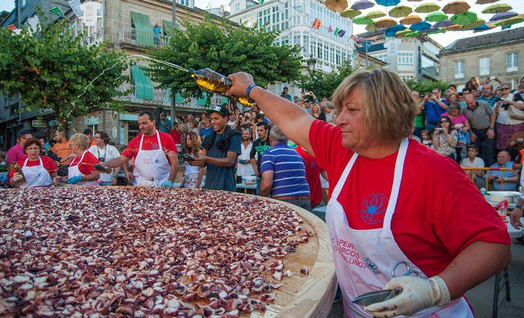 Mujer echando aceite sobre gran cantidad de pulpo