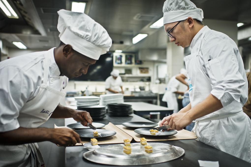 Dos de los cocineros emplatando el milhojas caramelizado de anguila ahumada, foie gras, cebolleta y manzana verde.