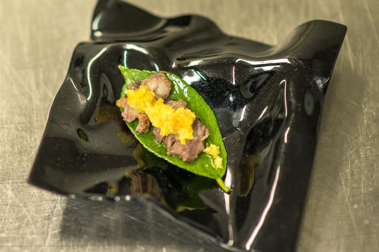 Carrillera de cordero sobre hoja de limonero y mole de naranja en salmuera, piñones y aove.