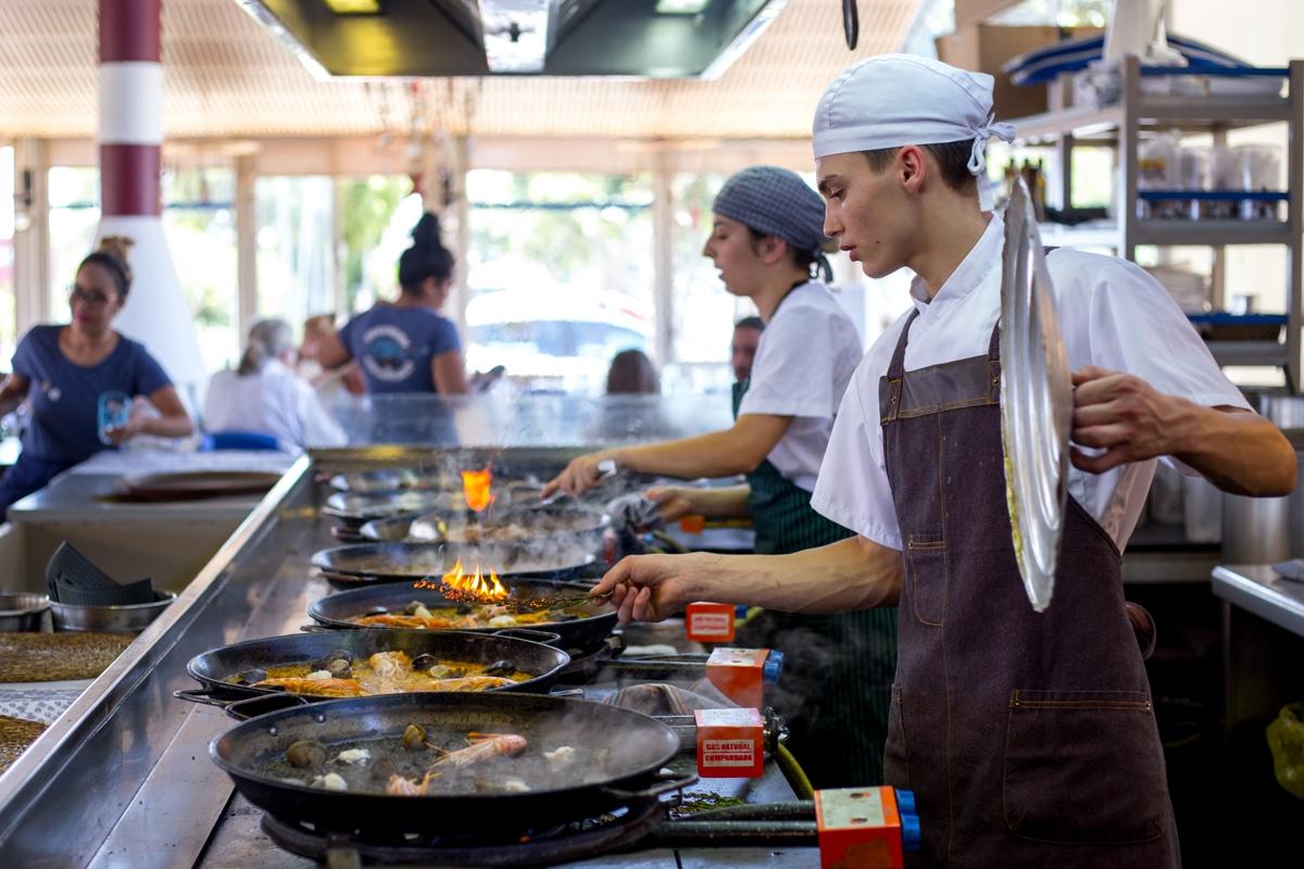 Los encargados de hacer del arroz en el Escribà comparten espacio con los clientes.