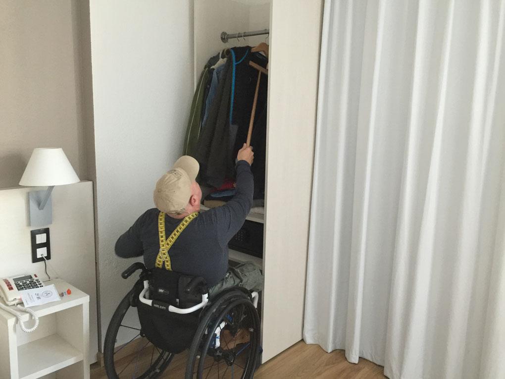 Hombre en silla de ruedas en una habitación accesible colgando ropa en un armario