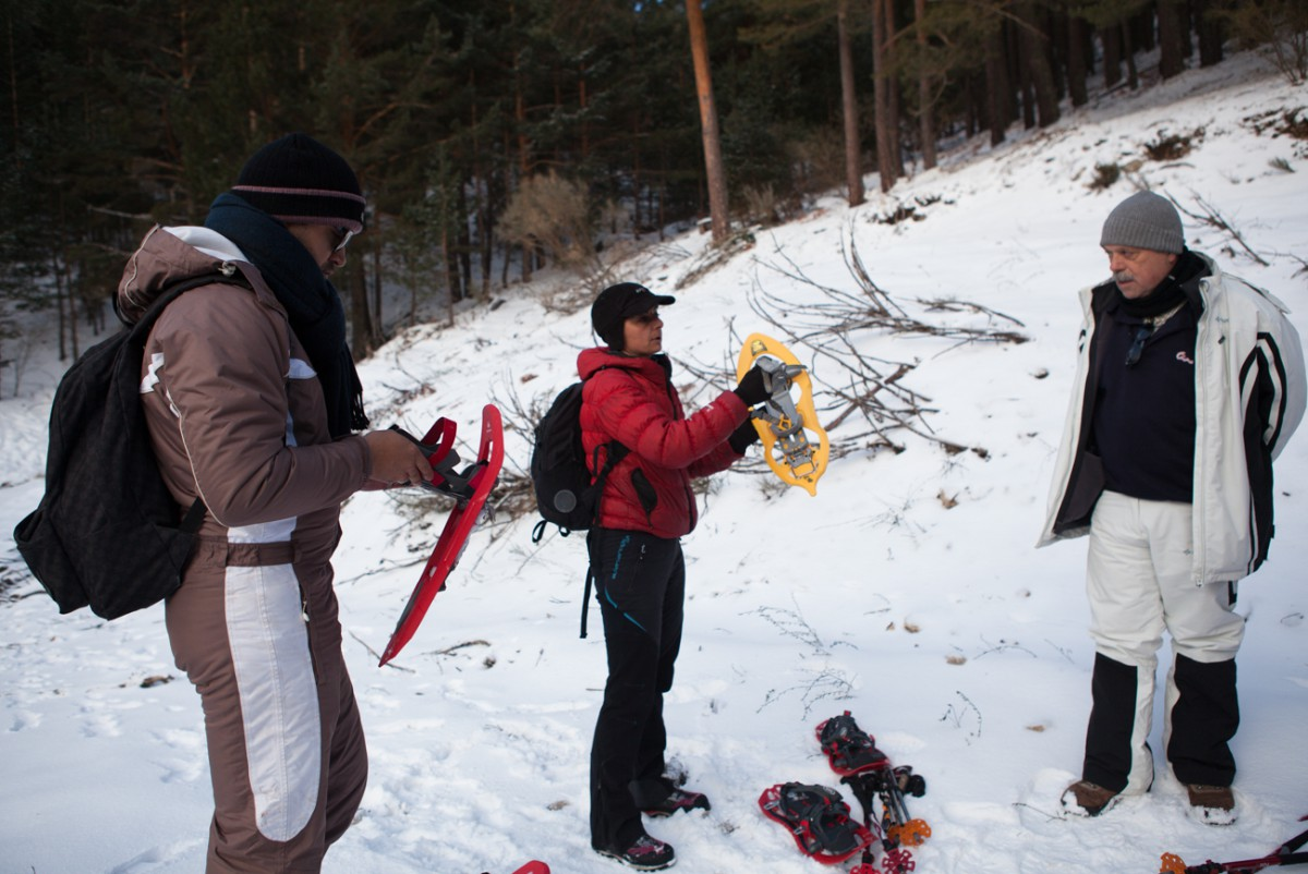 Nuria Hijano explica a los miembros del grupo cómo colocarse las raquetas.