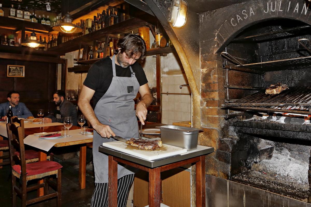 Uno de los hijos de Iñaki cortando la chuleta recién sacado de la parrilla de 'Casa Julián'.