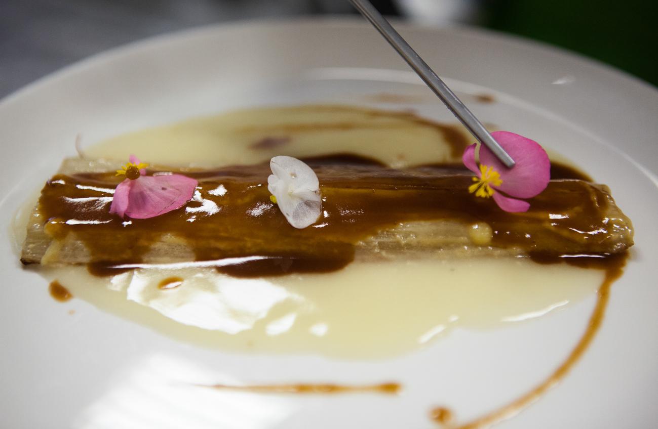 Cardo servido con una 'velouté' acompañado de jamón y almendra tostada.