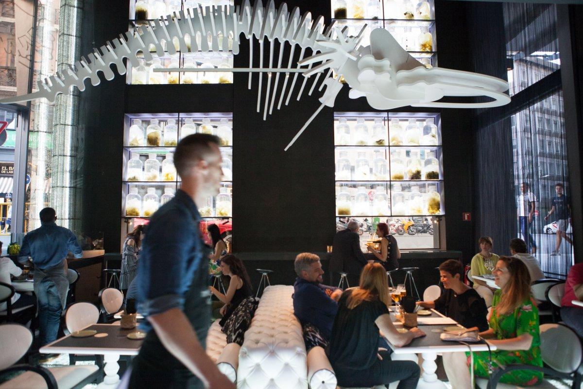 Un esqueleto artificial de ballena decora la sala del bar.
