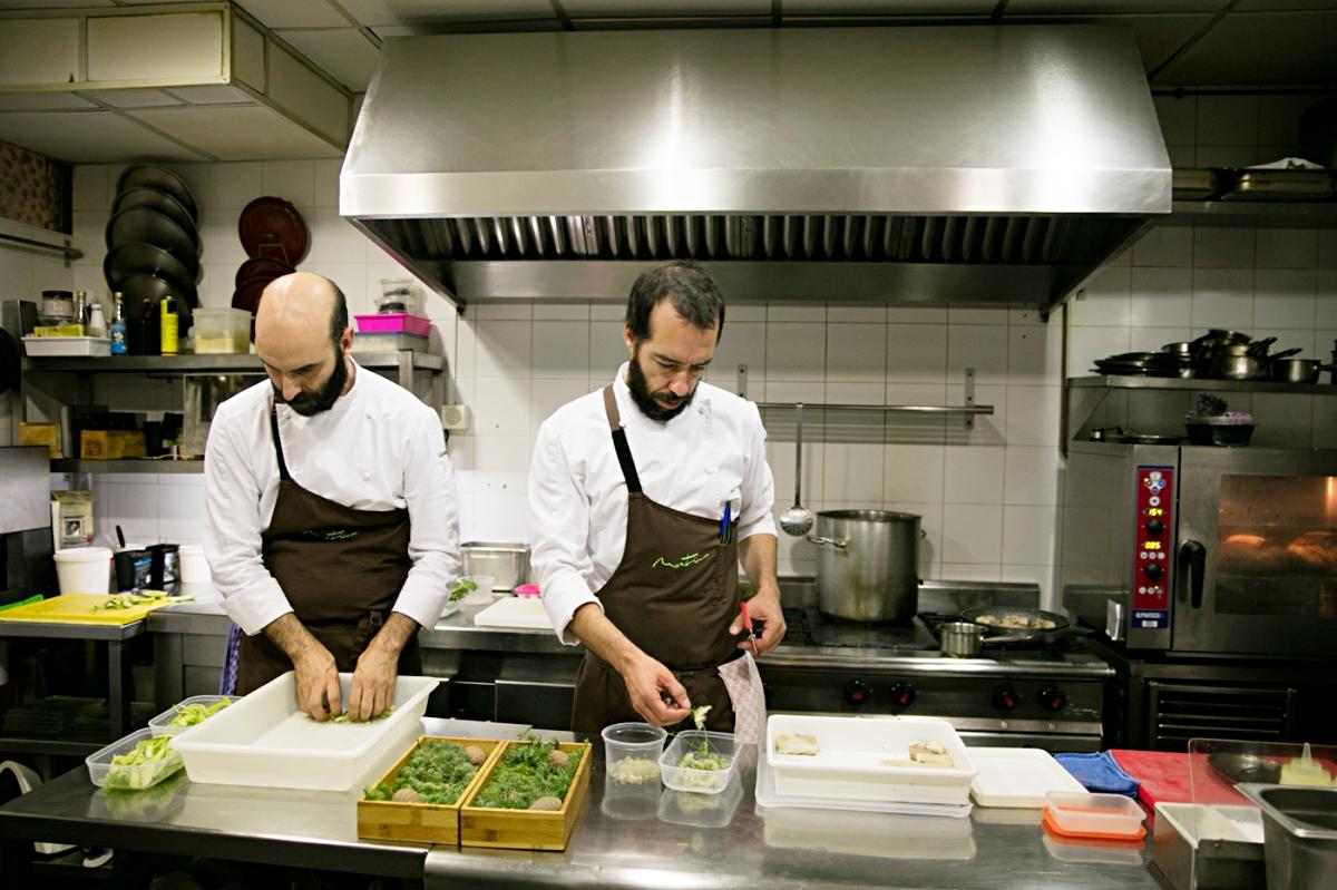 Luis y Daniel trabajando con varios elementos naturales para decorar los platos.