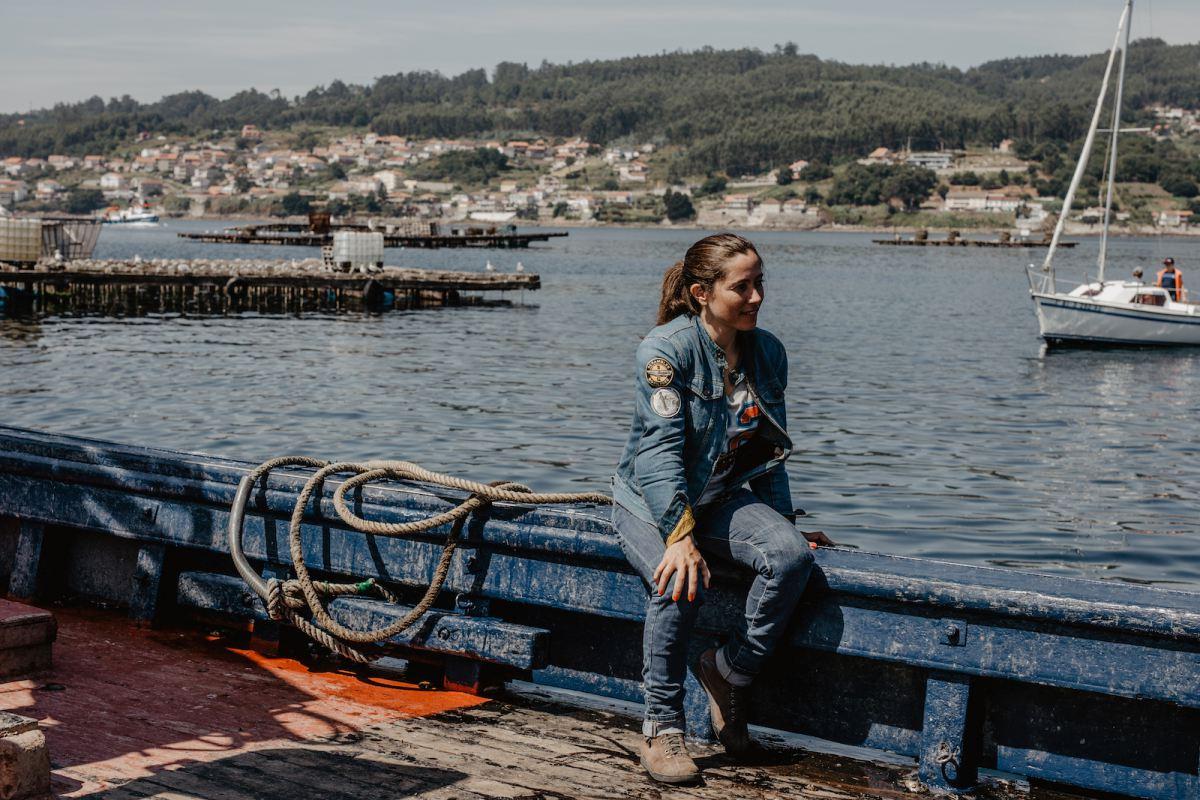 La periodista motera sobre una de las barcas con las bateas tras de sí y, al fondo, Combarro.