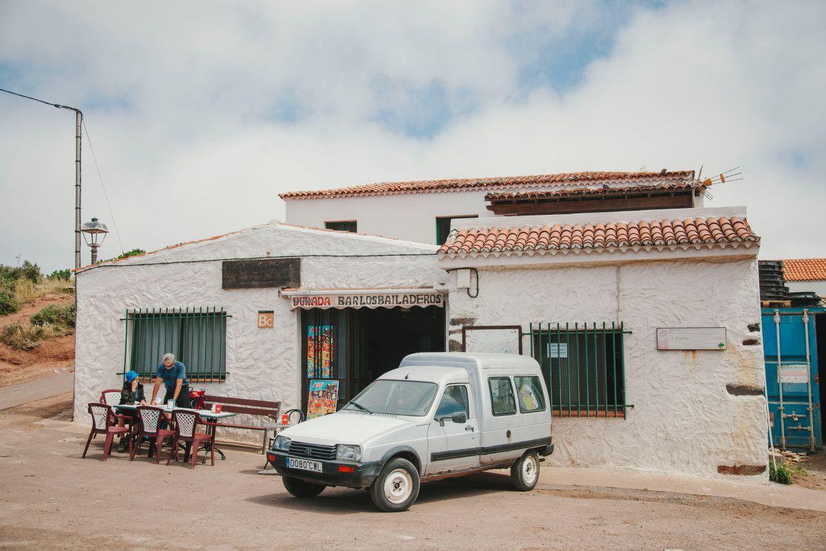 Una pareja de senderistas se sientan en la terraza del bar Bailaderos en el parque rural de Teno, Tenerife.