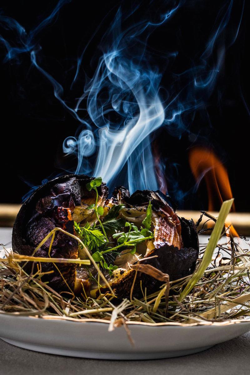 La cebolla negra, hecha a la brasa como los calçots y aliñada con garum casero y hierbas aromáticas.