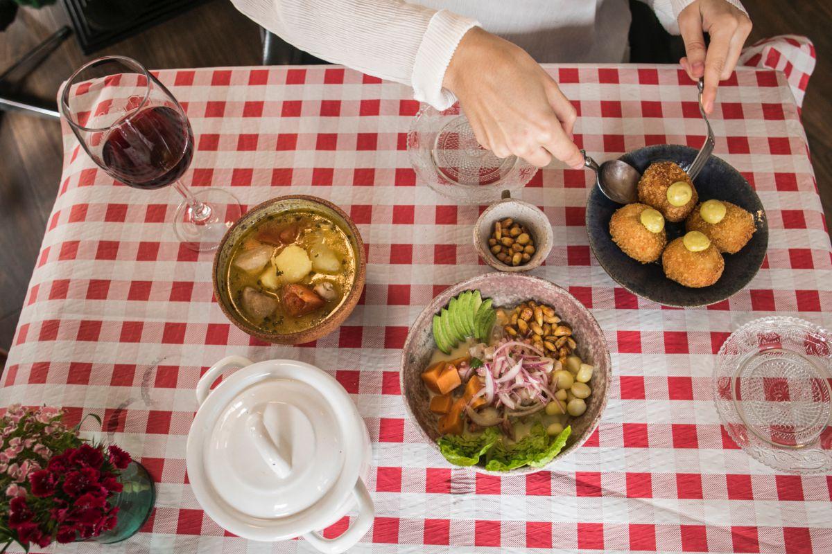 Sobre un mantel de cuadros, varios platos del restaurante peruano El Observatorio, en Valencia.