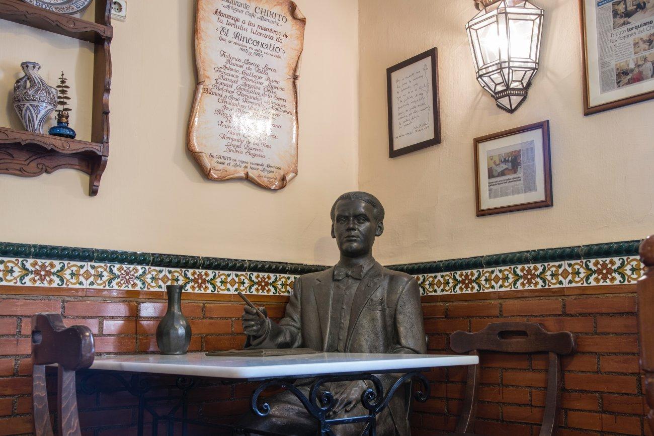 Una de las mesas del salón del restaurante 'Chikito', con una estatua del poeta Federico García Lorca.