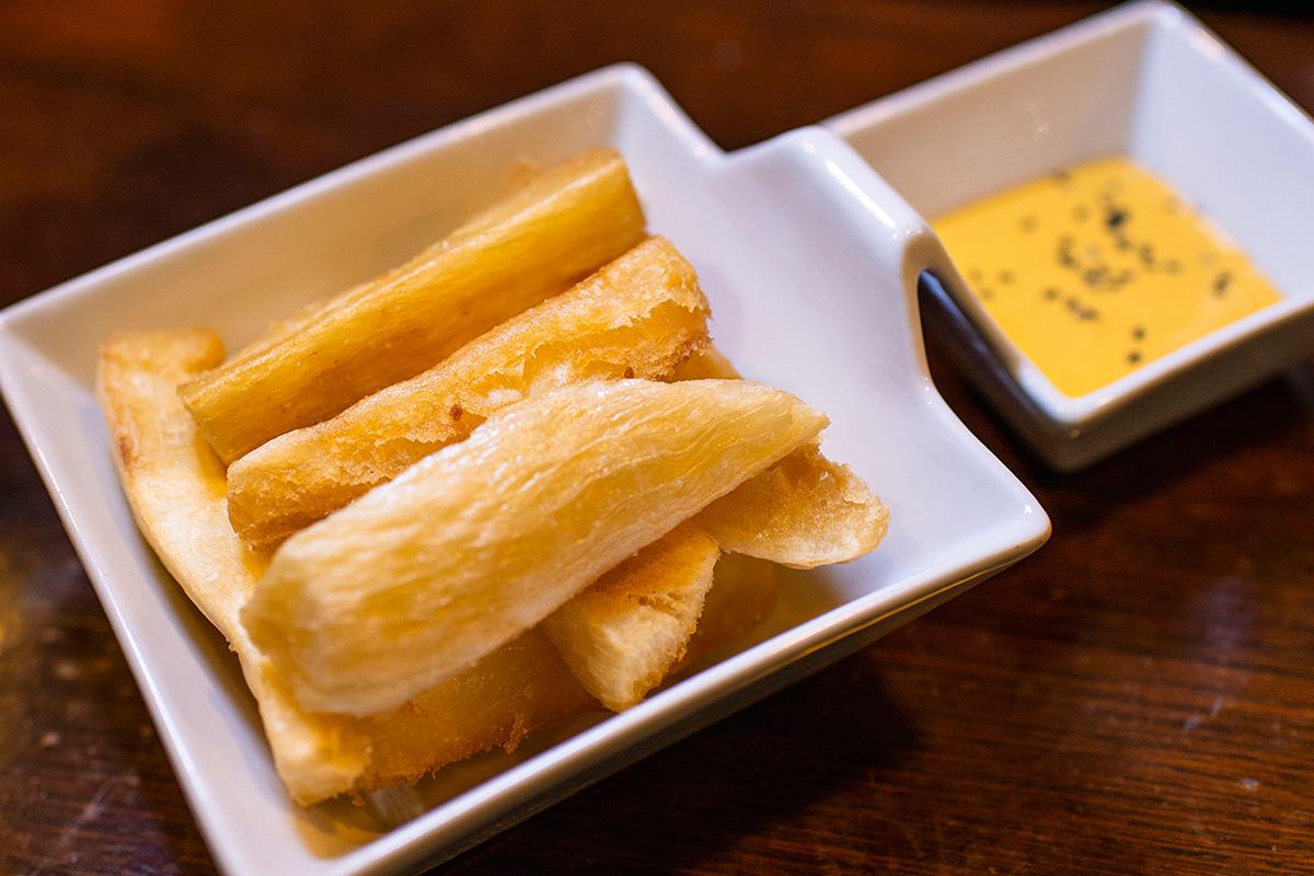 En 'El Inca' te sirven el cóctel con un aperitivo típico, en este caso yuca frita.