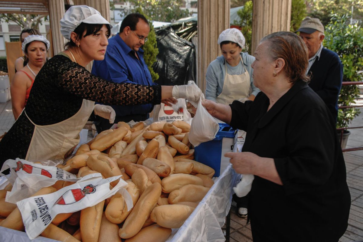 Repartiendo los panecillos que acompañan al guiso de la festividad del Santo Voto, en Puertollano, Ciudad Real.