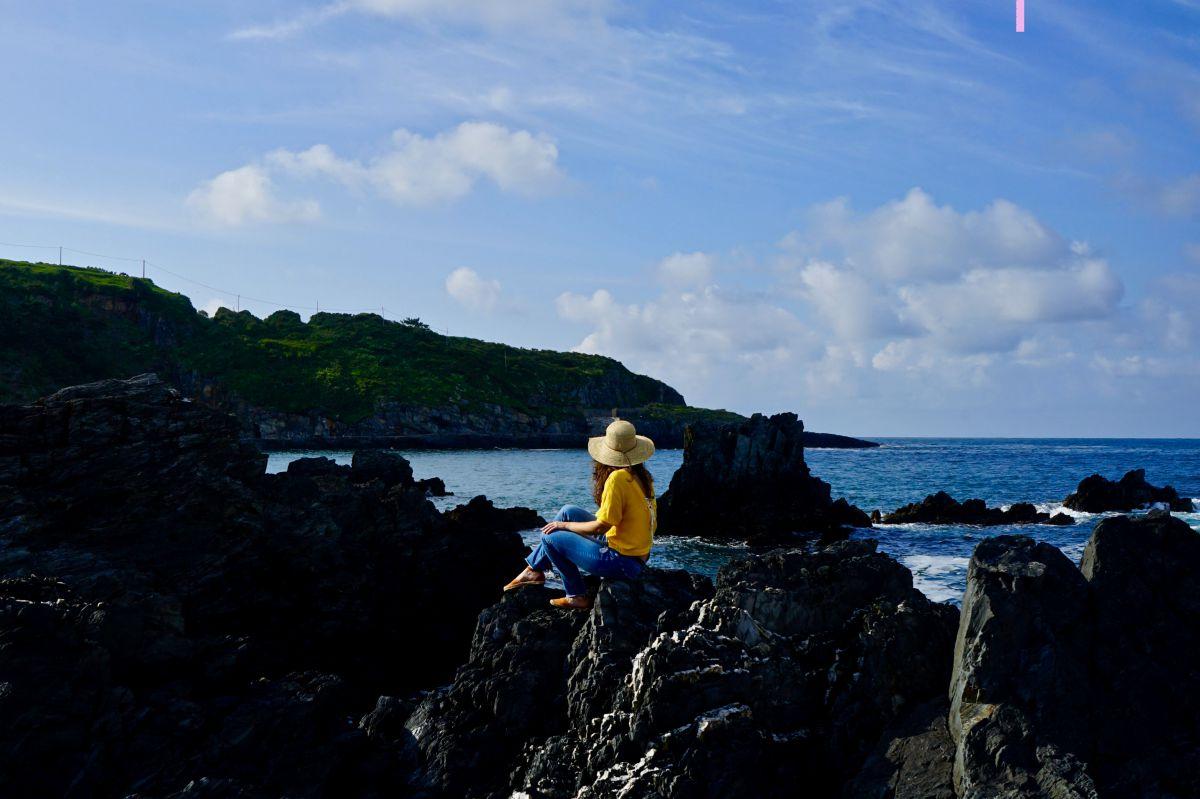 Una chica mira al mar en la playa de La Tercera, Luarca, Asturias.