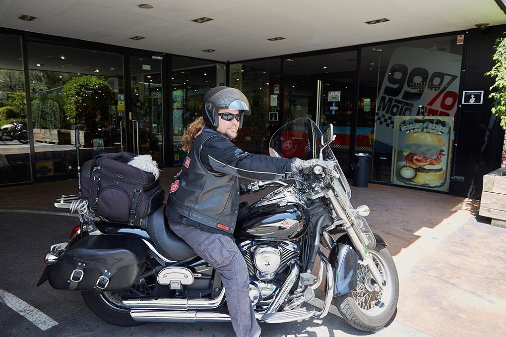 Motero arrancando la Harley en la puerta del '99% Moto Bar'.