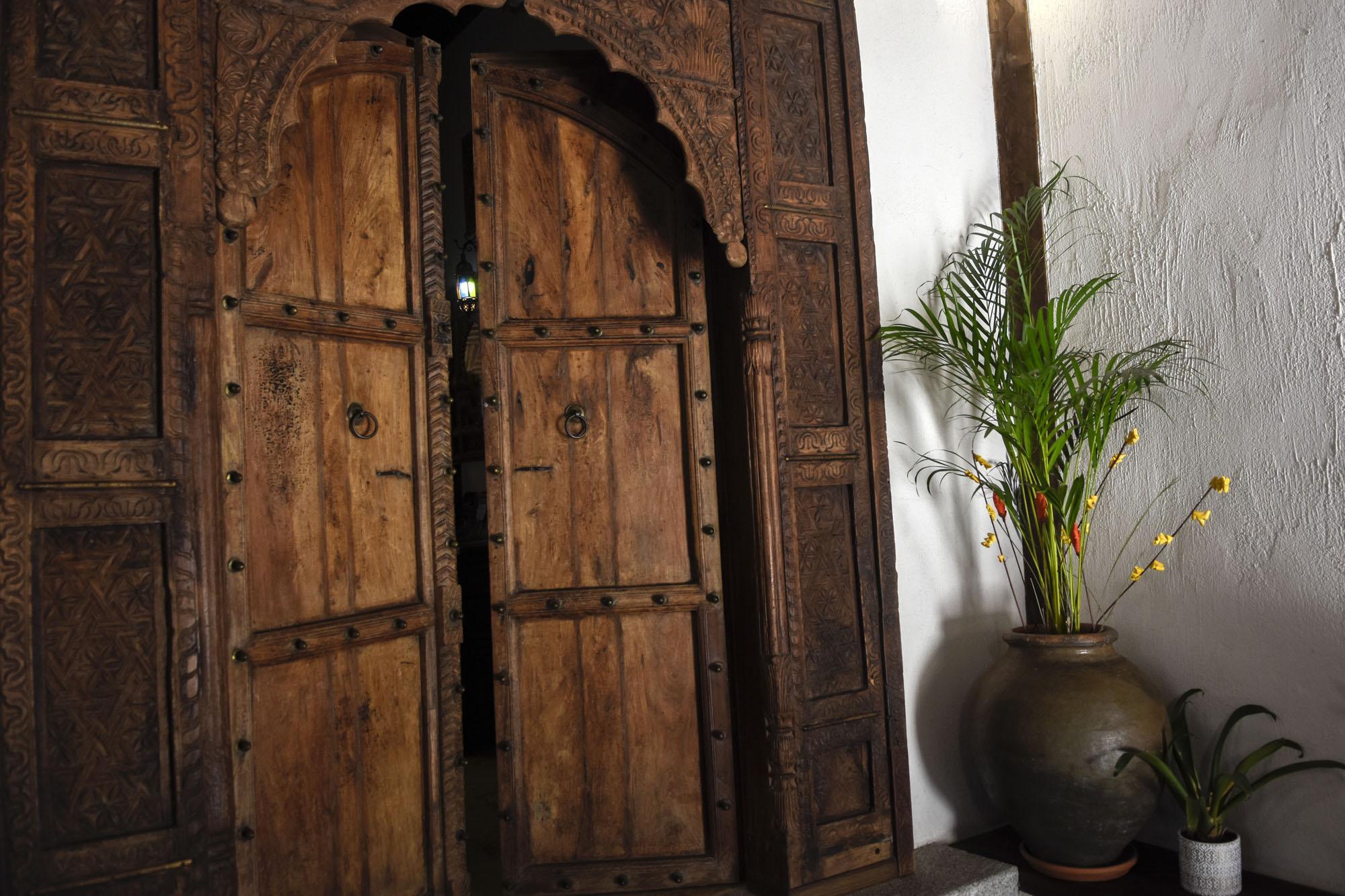 Puerta de Palosanto de India con planta de kentia.