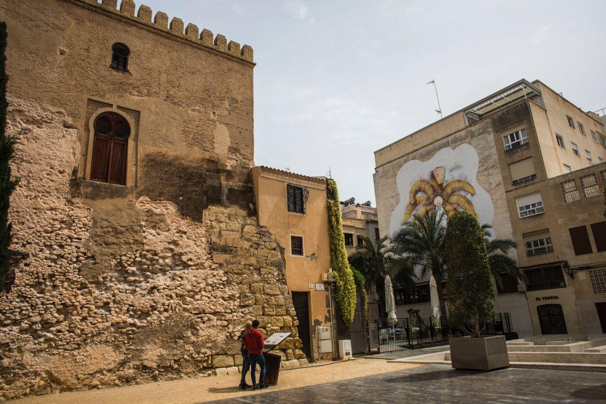 Una pareja lee un panel informativo de la Torre de la Calahorra, en Elche (Alicante).