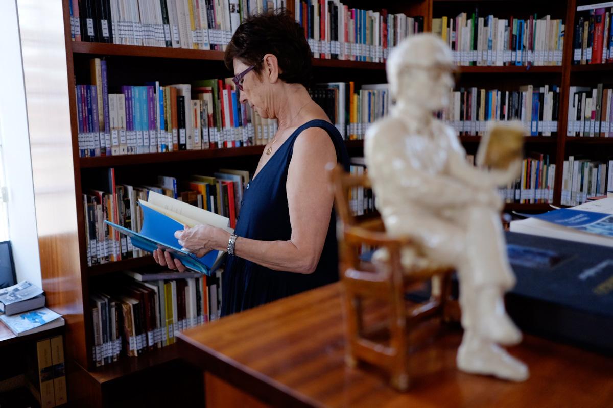 Pilar del Río con un libro en las manos y con la escultura del escritor leyendo en un primer plano.
