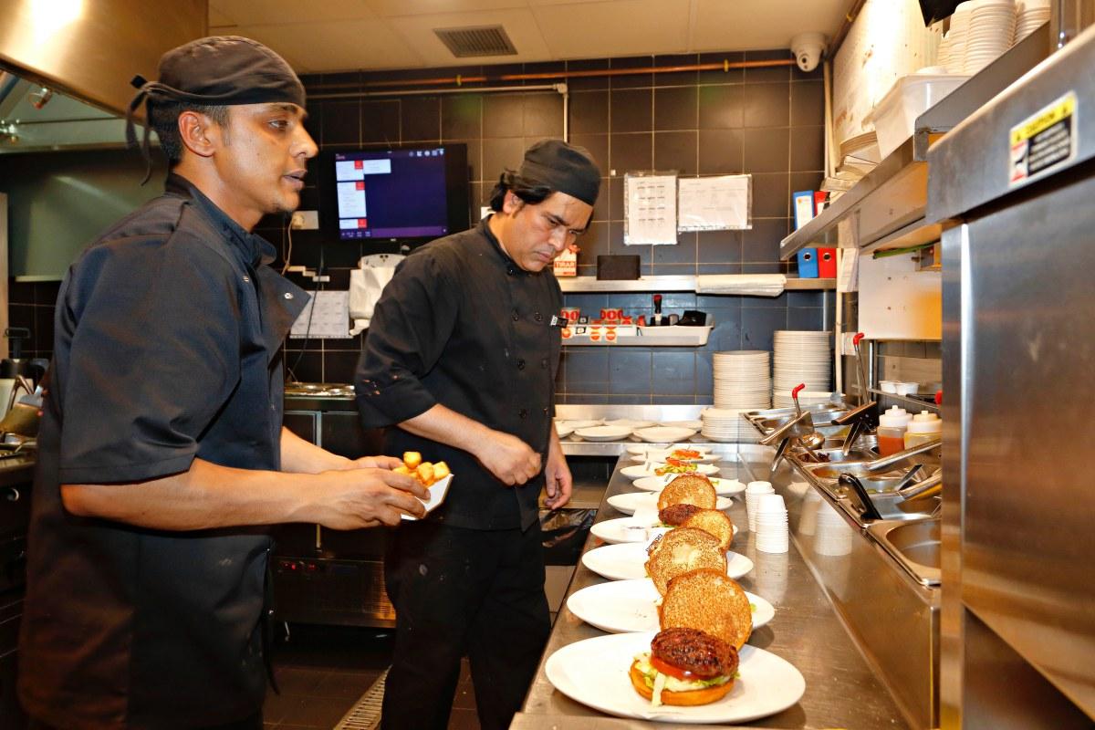 El ritmo en la cocina no cesa. El restaurante está lleno y las hamburguesas saltan de las brasas al plato.