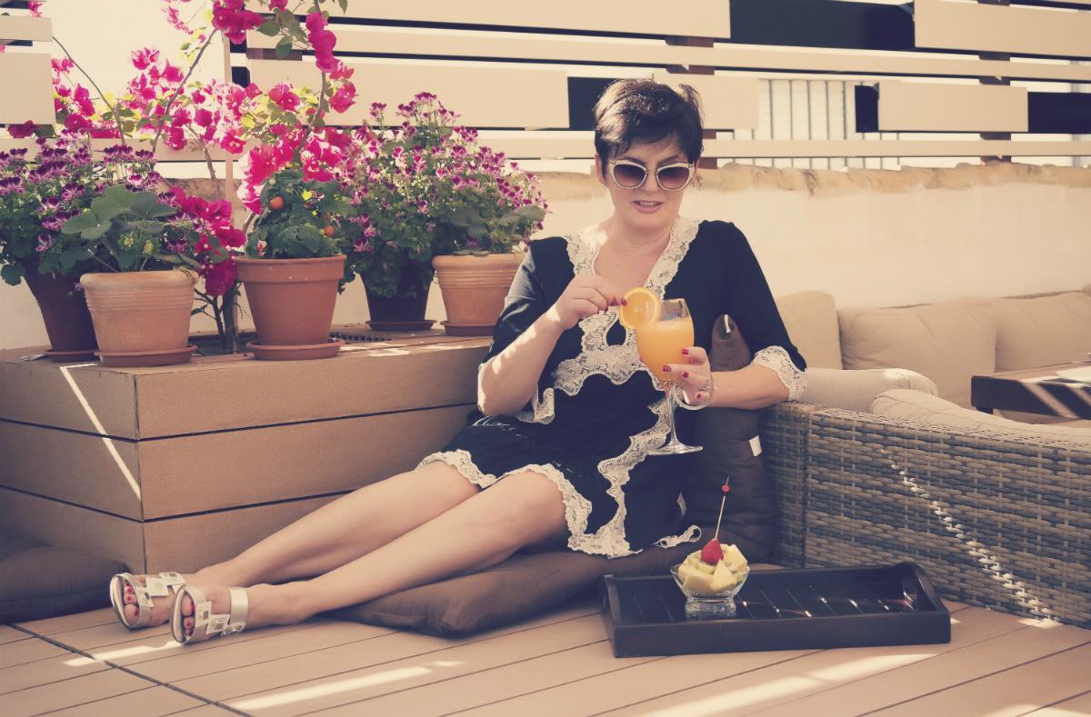 Mujer tumbada en la terraza tomando un cóctel