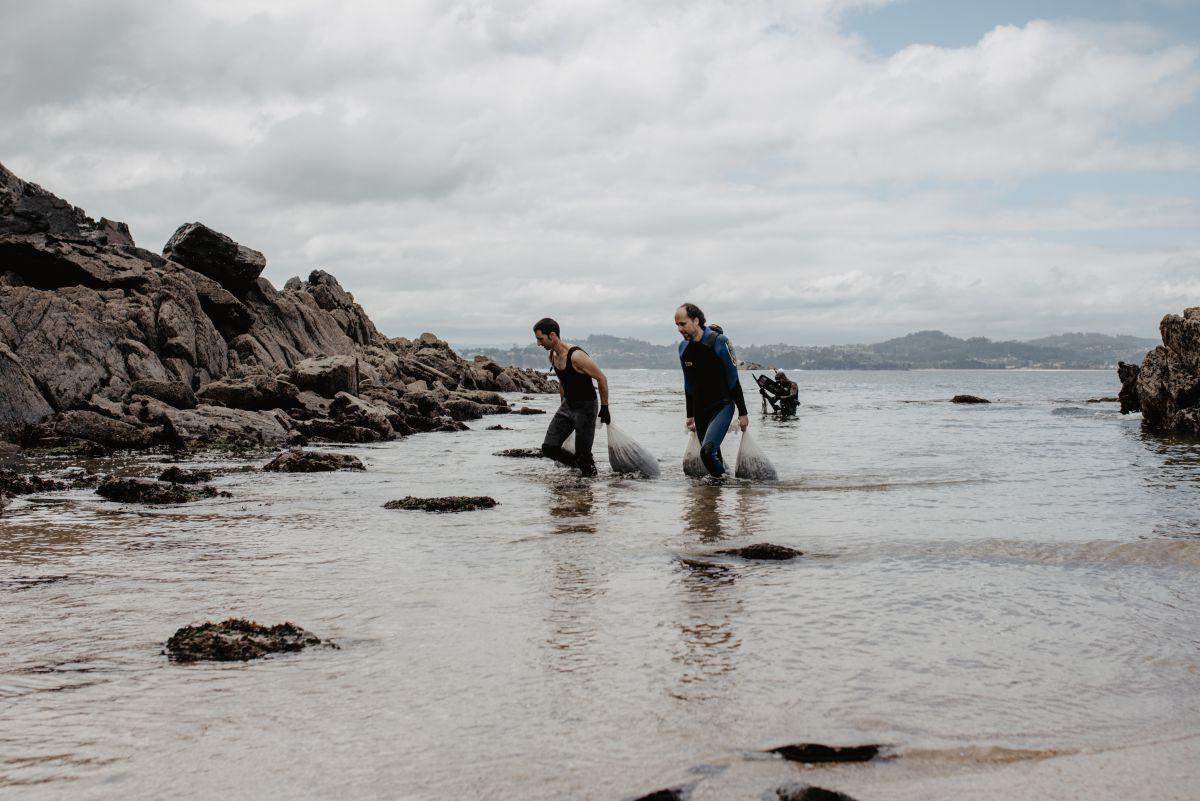 Sergio y Óscar, de Mar de Ardora, ayudan a sacar del agua los sacos que Alberto ha arrastrado hasta la orilla de la playa, en Galicia.