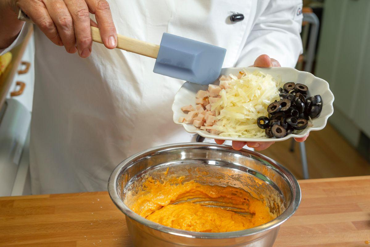 Echando las aceitunas a la masa del bizcocho de fiambre, aceitunas y queso con pimentón.