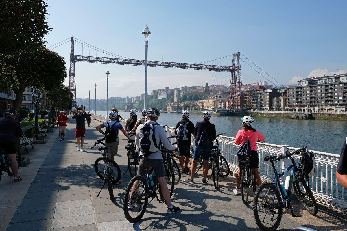 Un grupo de ciclistas observan el Puente Colgante cerca del monumento a Evaristo Churruca, en Getxo (Vizcaya).