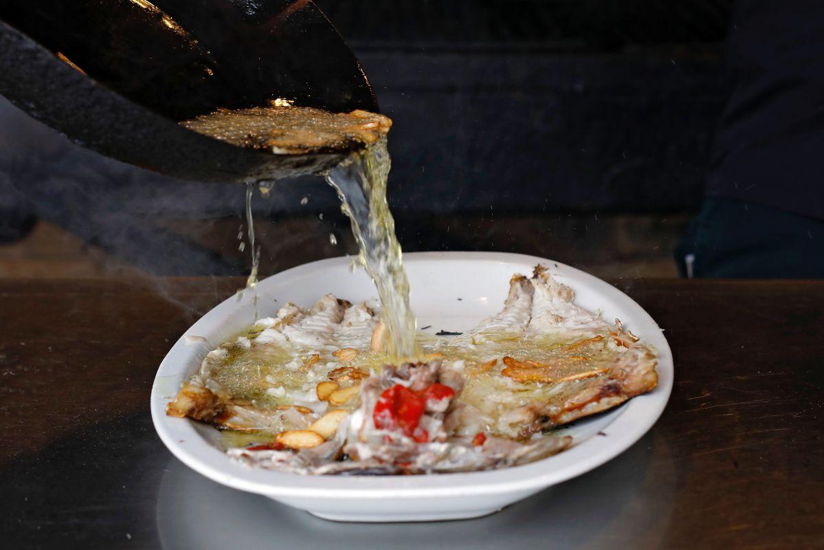 Vertiendo el aceite con ajos sobre el besugo abierto en el 'Bodegón Joxe Mari', en Orio (Guipúzcoa).