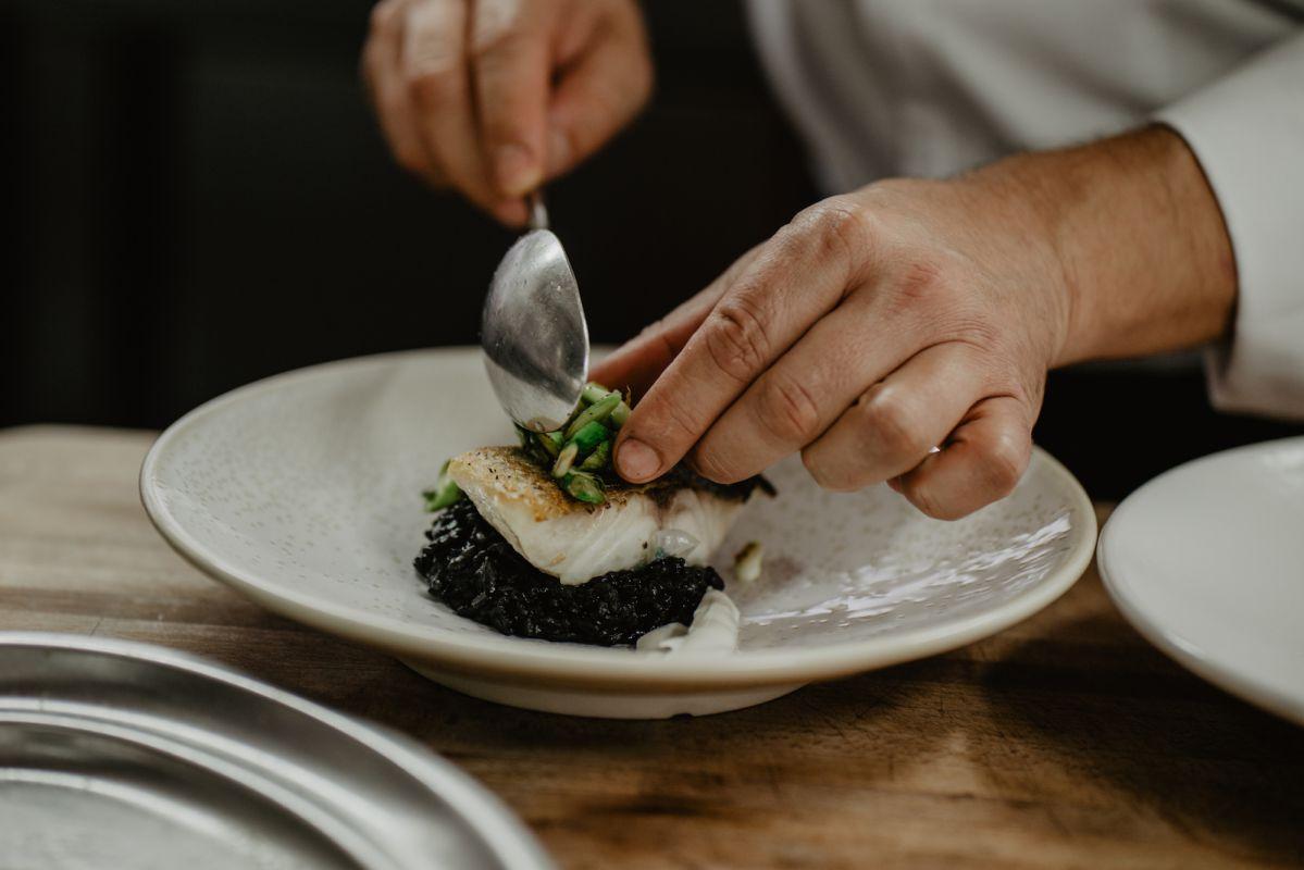 El pescado del día hoy es merluza con arroz negro, calamar y pil pil de ajo tostado y lima.