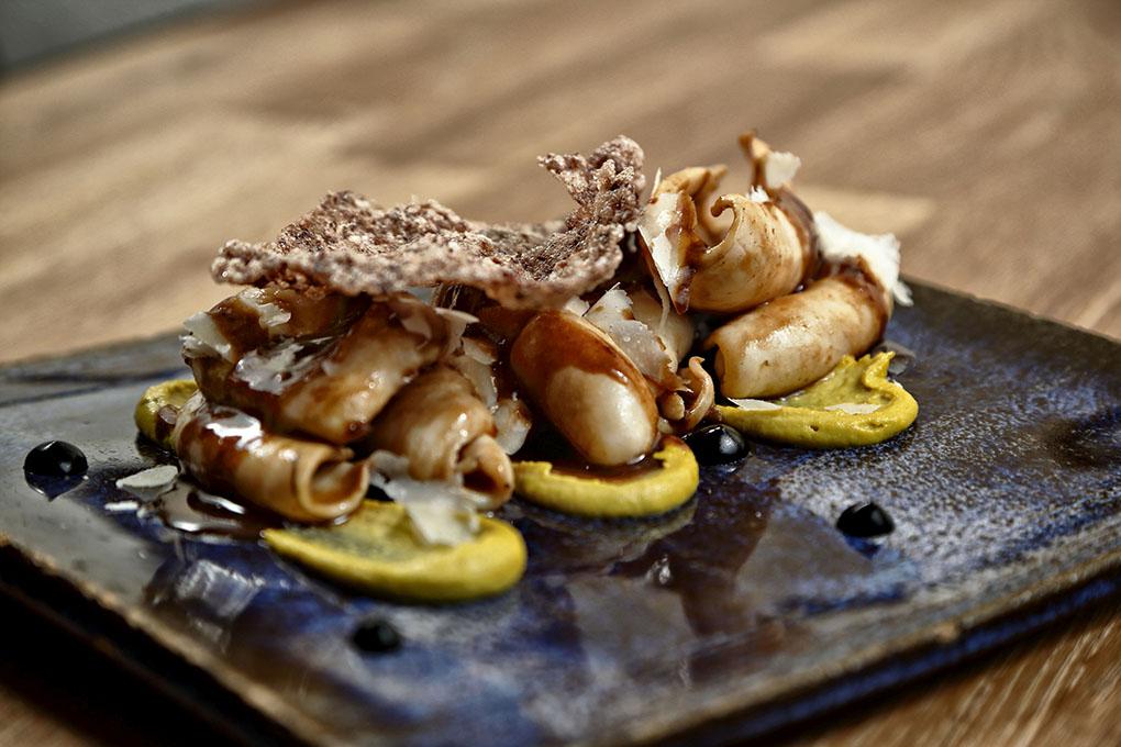 Chipirón sahariano con pistacho, parmesano, emulsión de jengibre y tinta.