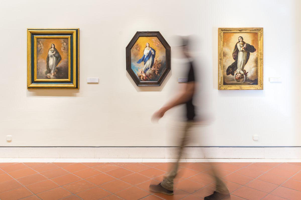 Un visitante recorre una de las salas del Museo de Bellas Artes de Sevilla donde cuelgan varias Inmaculadas de Murillo.