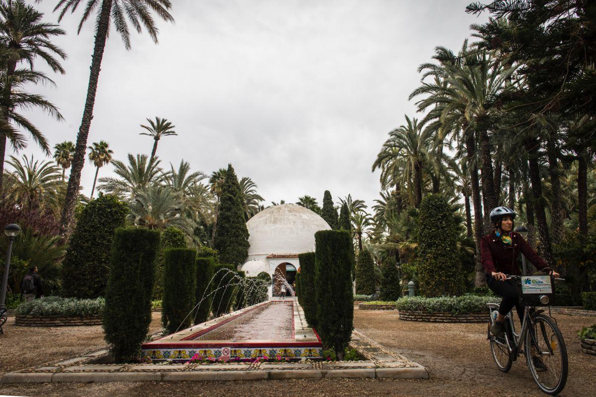 Pasando con la bici junto a una fuente del dentro de visitantes del parque municipal en Elche (Alicante).