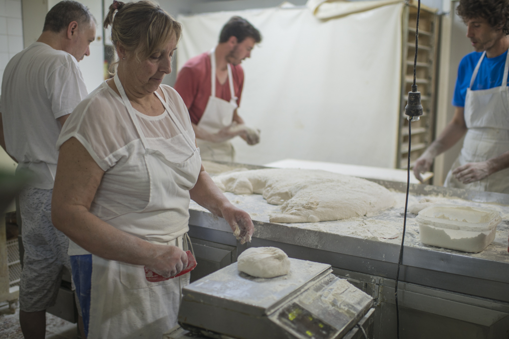 Ana pesa cada hogaza que van dividiendo de la masa ya levada después de dos fermentaciones y antes de darle forma.