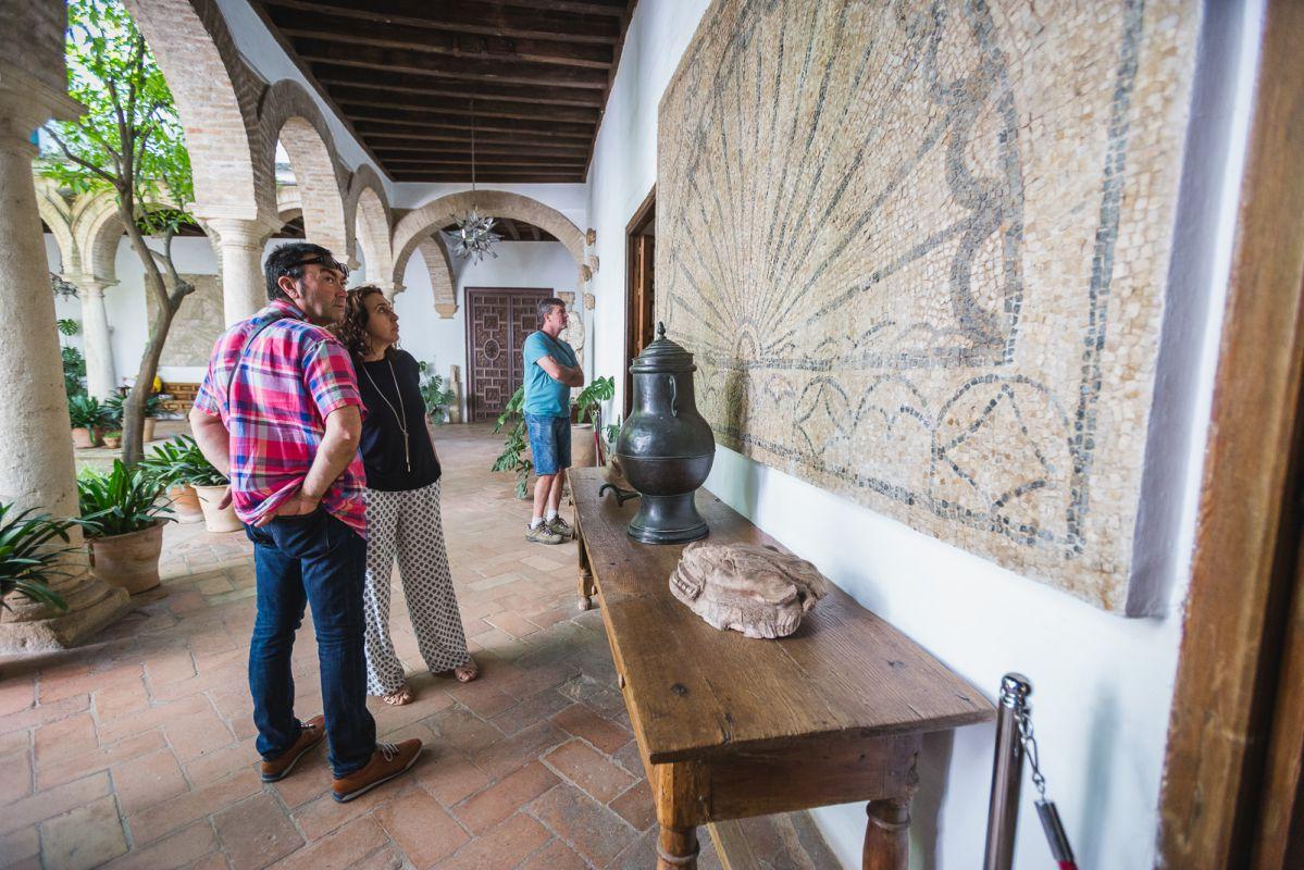 Una pareja admira uno de los mosaicos romanos repartidos por todo el palacio.