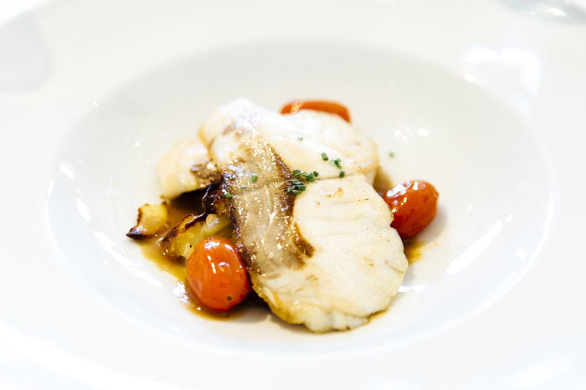 La lubina de la lonja de Palamós, con patatas al horno confitadas y cebolla de Figueres.