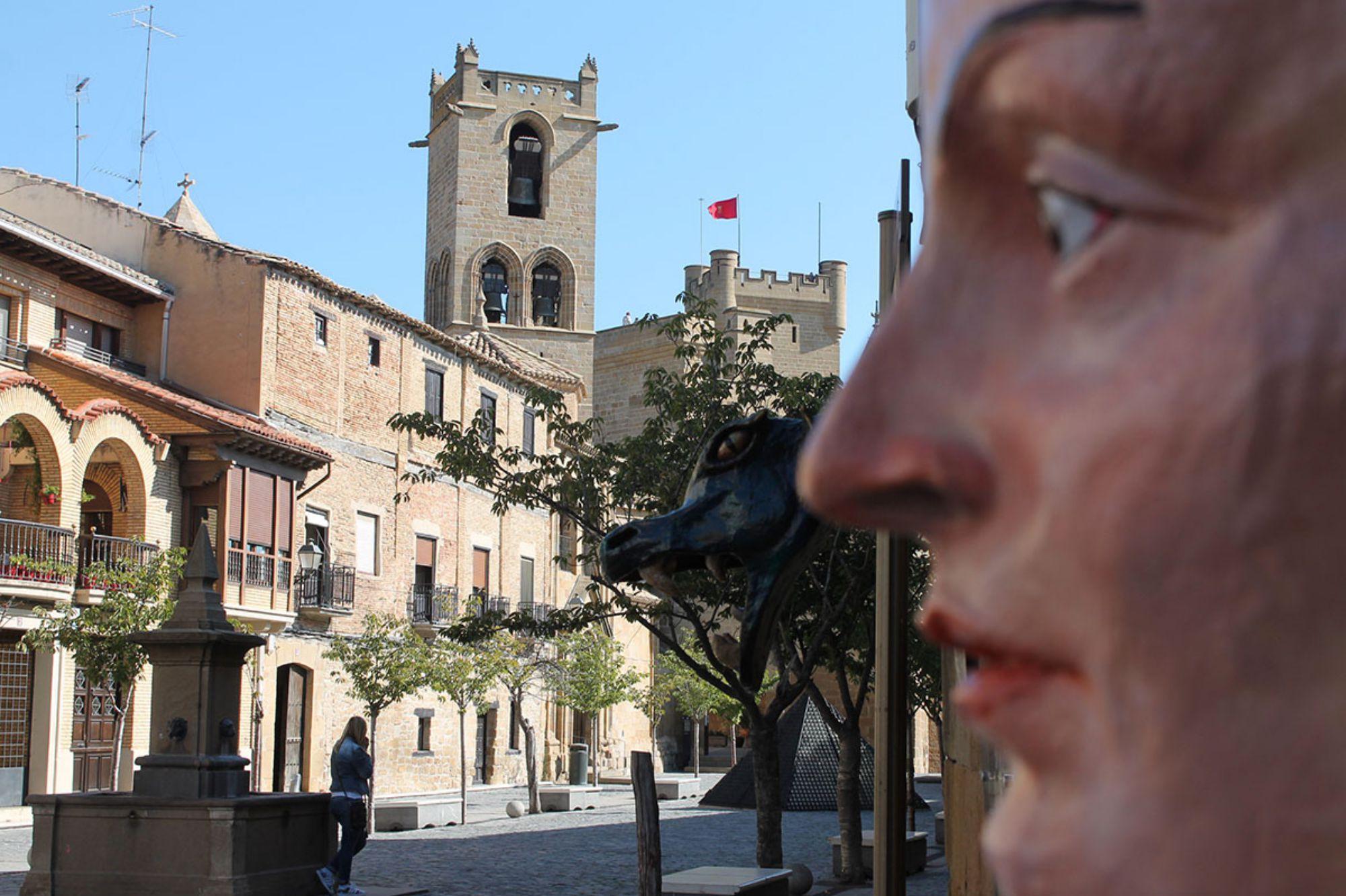 Una herbólera (una bruja local) observa la plaza de Olite, con el castillo al fondo. Foto: Edu Sánchez.