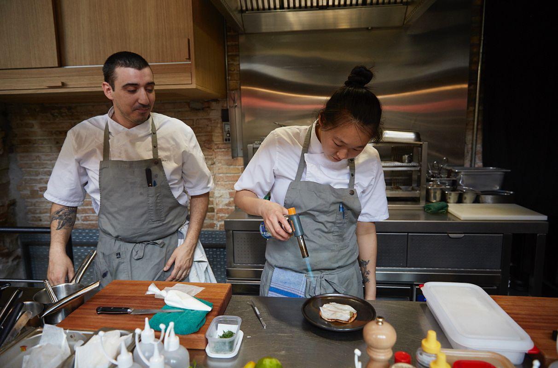 Los chefs Arnau Muñío y Shu Zhang en la cocina de la barra del restaurante Direkte Boquería, en Barcelona.