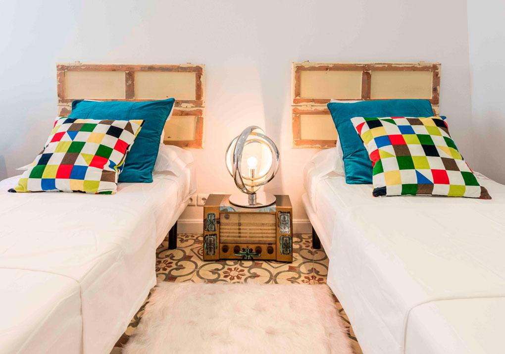 Dos camas individuales con una mesilla y una lámpara en medio