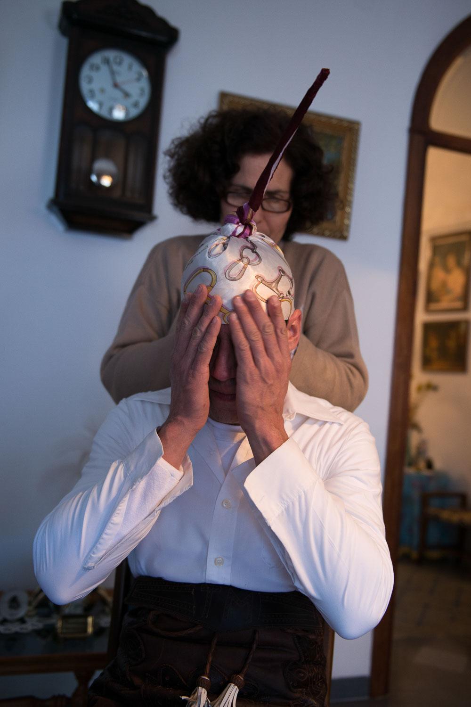 Mujer preparando a un hombre con el traje típico de la fiesta. Foto: Manuel Ruiz Toribio.