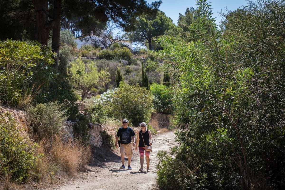 Una pareja de turistas camina por el paseo ecológico de Calpe, en Alicante.