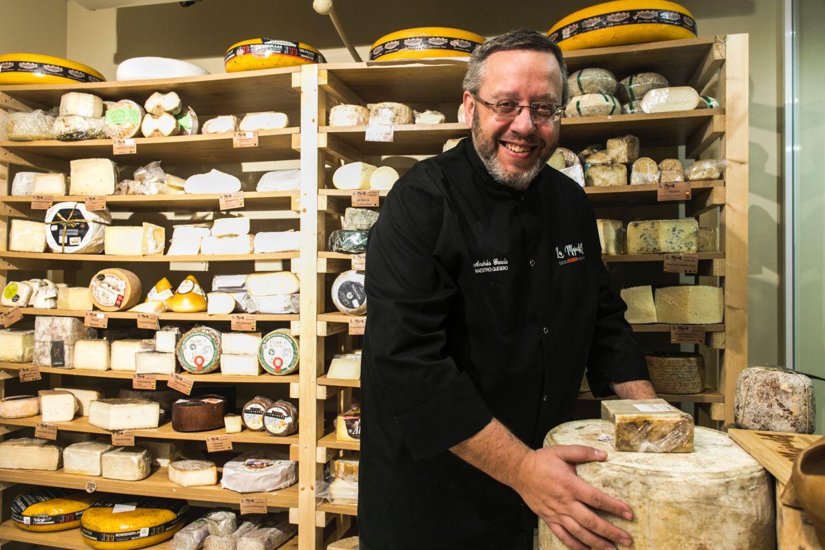 Andrés García rodeado de los quesos curados de la cava.