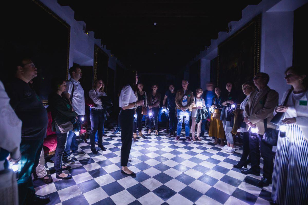 La guía de Engranajes Culturales recibe a los visitantes a la entrada del Hospital de la Caridad durante la visita nocturna, en Sevilla.