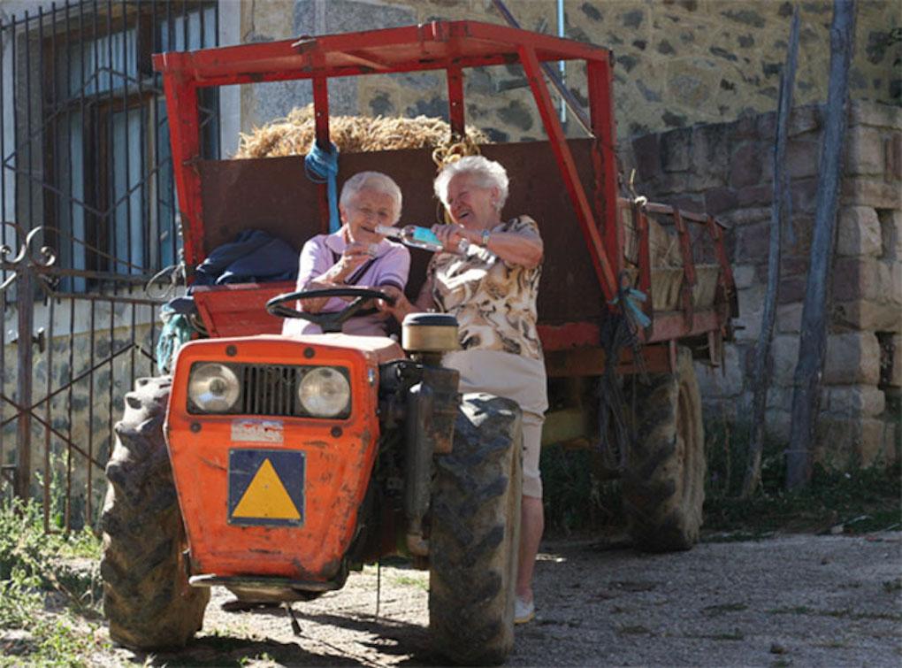 Fidela y Severina disfrutando de un orujo montadas en un motocultor. Foto: Santiqueros.