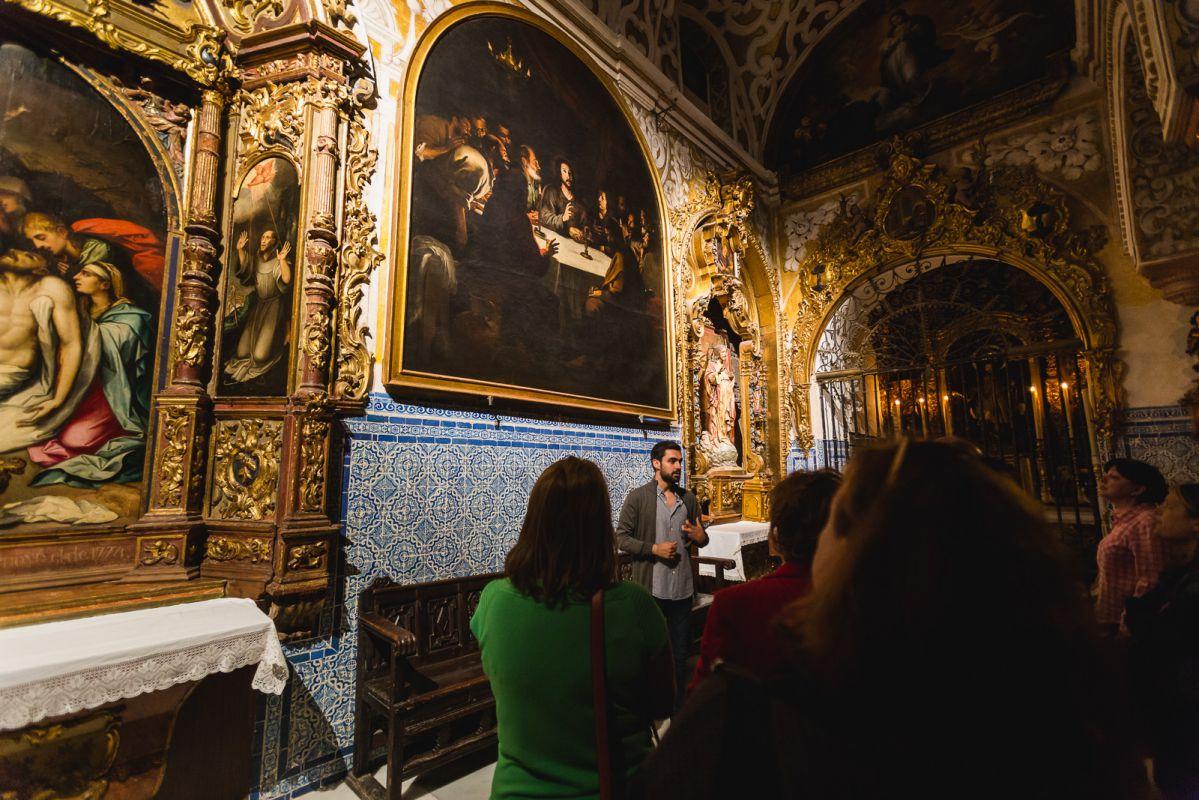 El guía muestra el cuadro de La Santa Cena de Murillo en la iglesia de Santa María La Blanca durante la visita nocturna, en Sevilla.