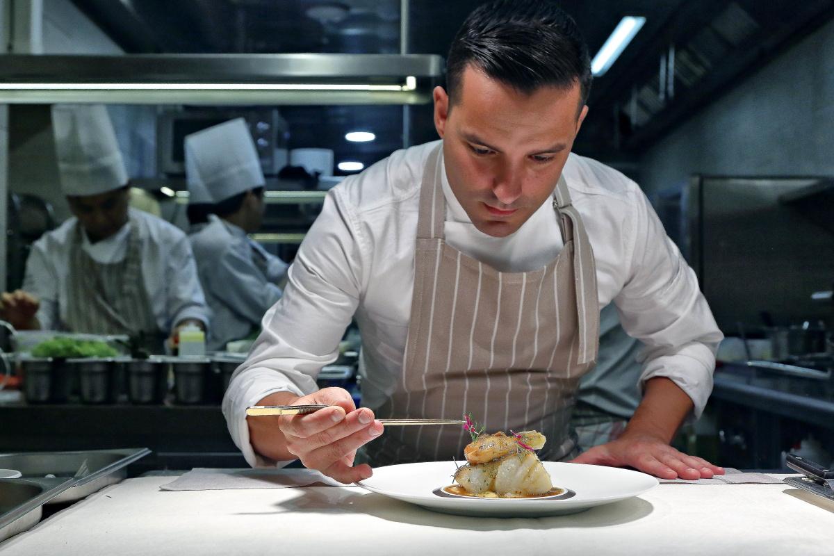 El chef José Manuel de Dios dando los últimos retoques a un plato de bacalao.