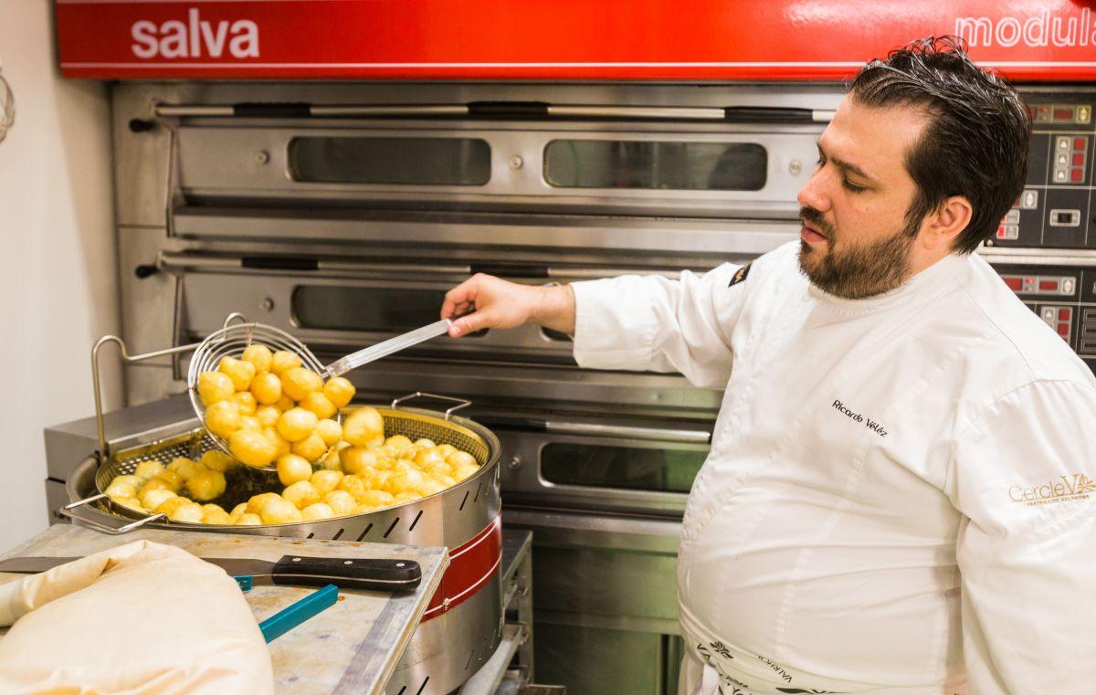 El chef remueve los buñuelos para que vayan tomando forma.