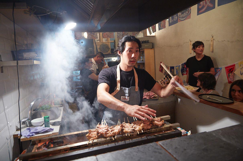 El cocinero Luis Chang maneja la barbacoa del restaurante pop up de barbacoa japonesa del chef Aitor Olabegoya en Poble Sec (Barcelona).