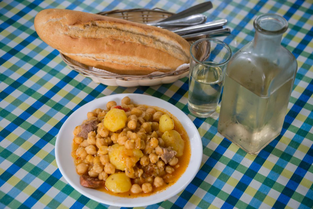 Plato de garbanzas junto al vino en una mesa del guachinche Las Galanas, en Tenerife.